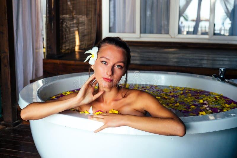 Kvinnliga sexiga brunetslappningar i bad med tropiska blommor utomhus på lyxhotellet Hälso- och sjukvård med ekologisk hud royaltyfri foto