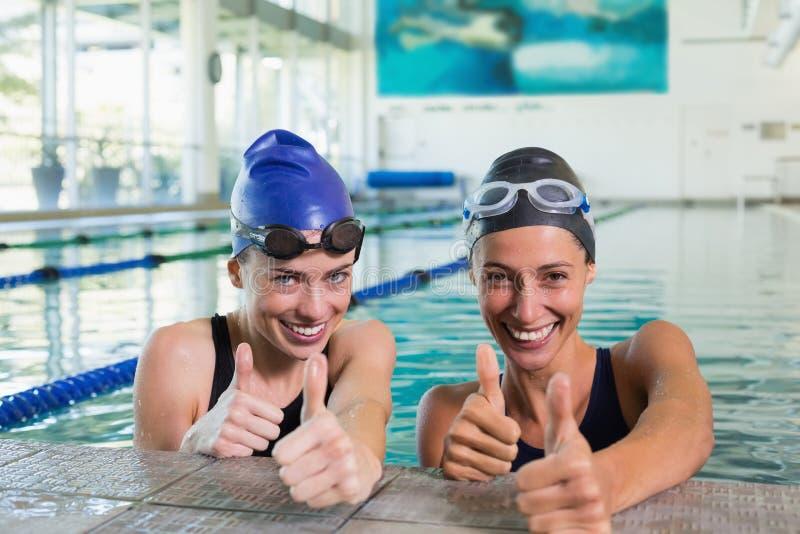 Kvinnliga simmare som ler på kameran i simbassängen arkivfoto