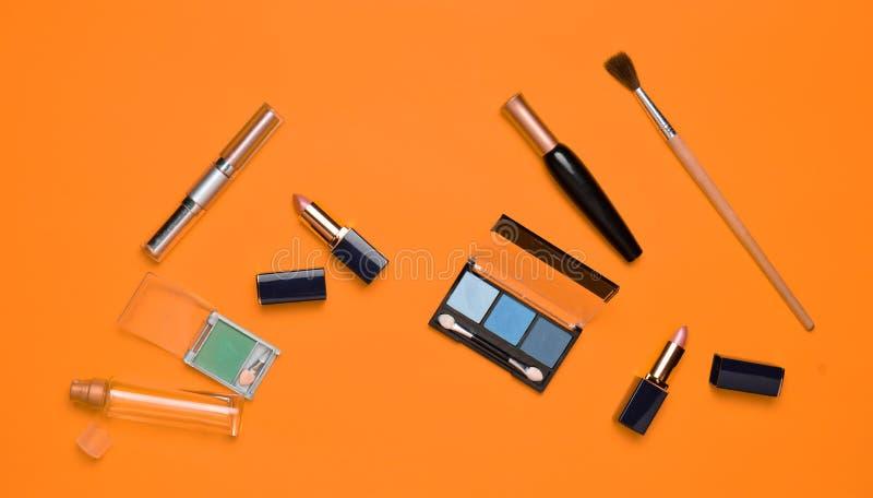 Kvinnliga skönhetsmedel för sminkorientering på en orange bakgrund Skönhetsmedlet skuggar, sminkborsten, ögonskuggaläppstift, dof royaltyfri bild