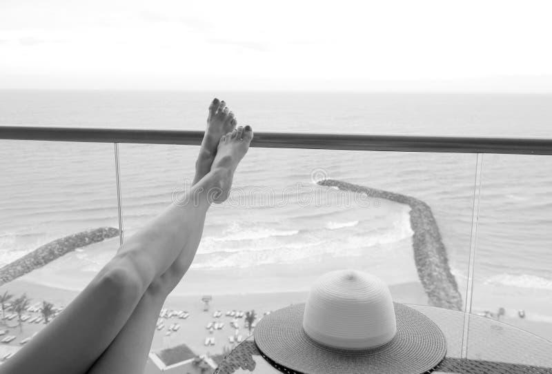 Kvinnliga spensliga långa ben på balkongen Semestern vilar arkivbilder
