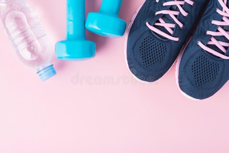 Kvinnliga sportskor, blåa hantlar och flaska av vatten på en rosa bakgrund med kopieringsutrymme, bästa sikt fotografering för bildbyråer