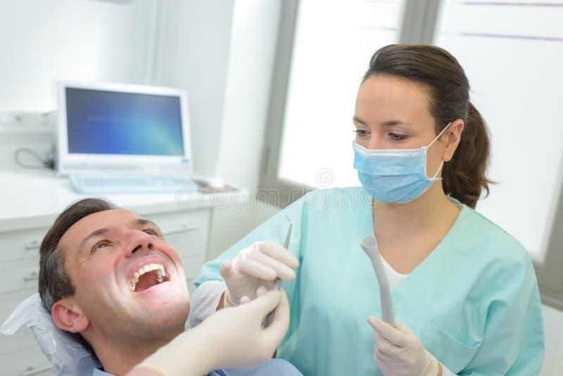 Kvinnliga tandläkare som undersöker och arbetar på den manliga patienten royaltyfria foton