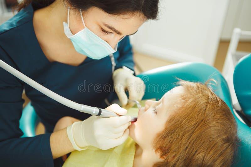 Kvinnliga tandläkareborrandetänder pysen Ung patient på en tidsbeställning för doktors` s arkivbild