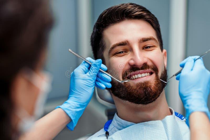Kvinnliga tandl?kare som arbetar p? ung manlig patient Selektivt fokusera Slapp fokus royaltyfria foton