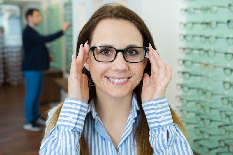 Kvinnliga testa nya exponeringsglas i optikerlager royaltyfri fotografi