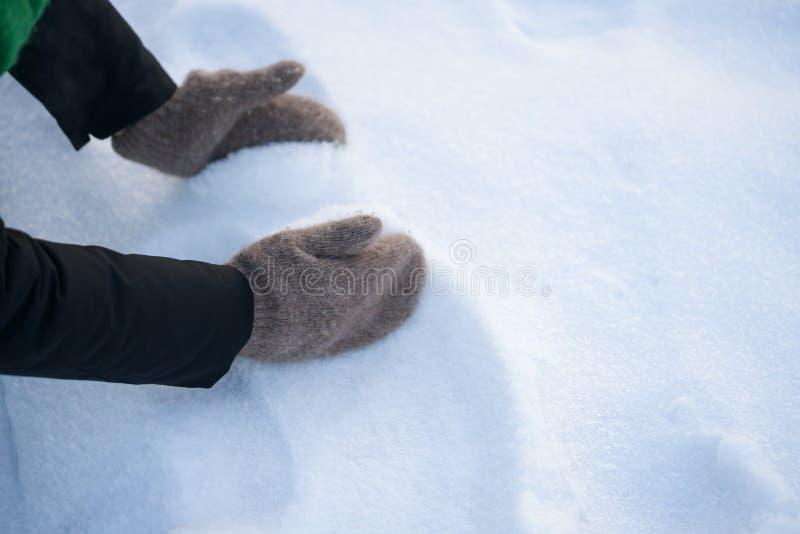 Kvinnliga tonåriga händer i tumvanten som griper ny snö royaltyfri foto