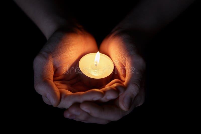Kvinnliga tonåriga händer som rymmer den brinnande stearinljuset royaltyfri foto