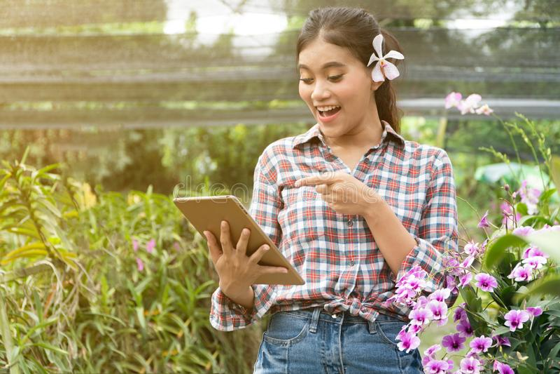 Kvinnliga trädgårdsmästare bär plädskjortor Det fanns orkidér som upp väljer öronen, handen som rymmer minnestavlan och pekar fin fotografering för bildbyråer