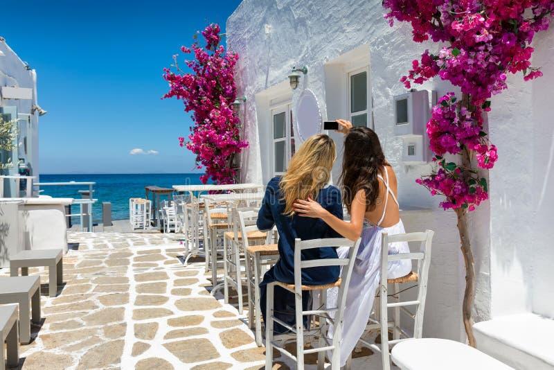 Kvinnliga turister tar ett selfiefoto i de kalkade gränderna av den Naousa byn på Paros arkivbilder