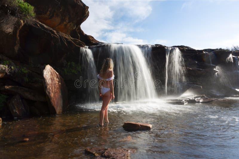 Kvinnliga undersökande och tyckande om vattenfall och att vagga tips i natur fotografering för bildbyråer