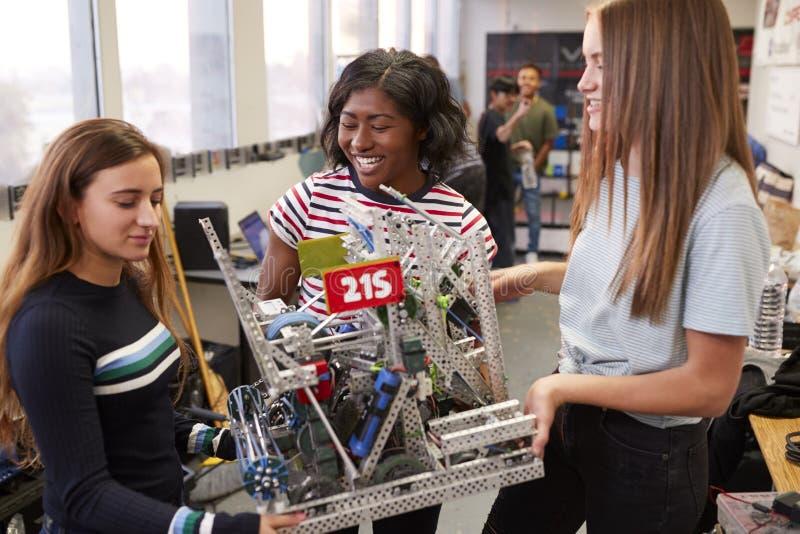 Kvinnliga universitetsstudenter som bär maskinen i vetenskapsrobotteknik eller iscensätter grupp arkivbilder