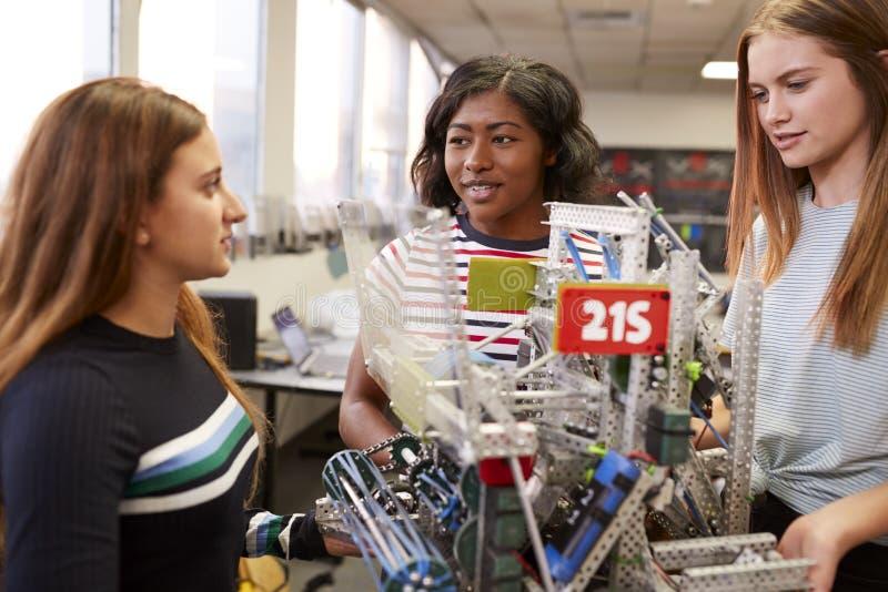 Kvinnliga universitetsstudenter som b?r maskinen i vetenskapsrobotteknik eller iscens?tter grupp arkivbilder