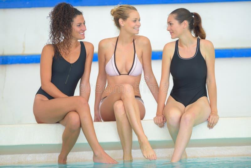 Kvinnliga vänner för lycklig grupp som har gyckel i simbassäng royaltyfria foton
