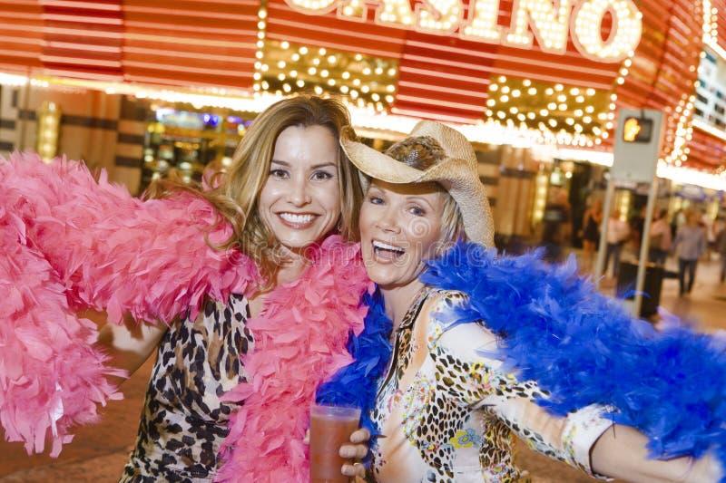 Kvinnliga vänner med Boaanseende mot kasino royaltyfri foto