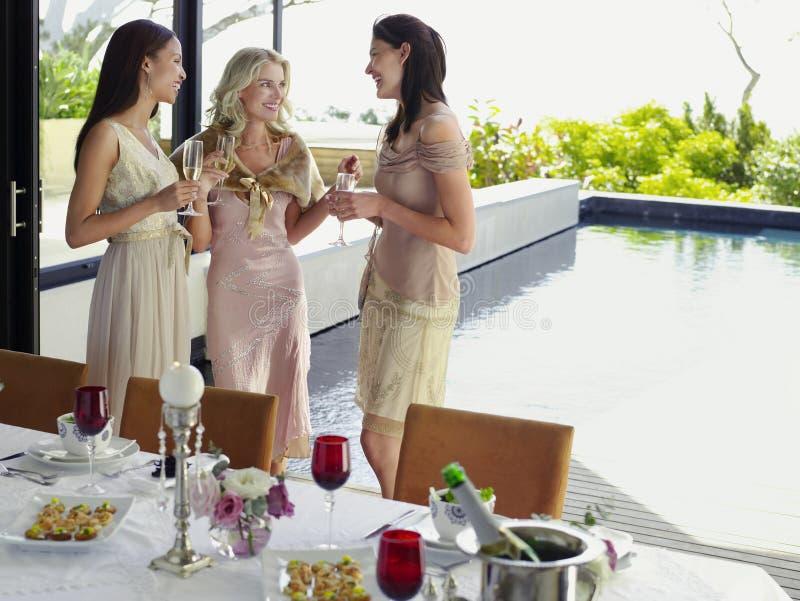 Kvinnliga vänner med Champagne Flutes At Dinner Party royaltyfria foton