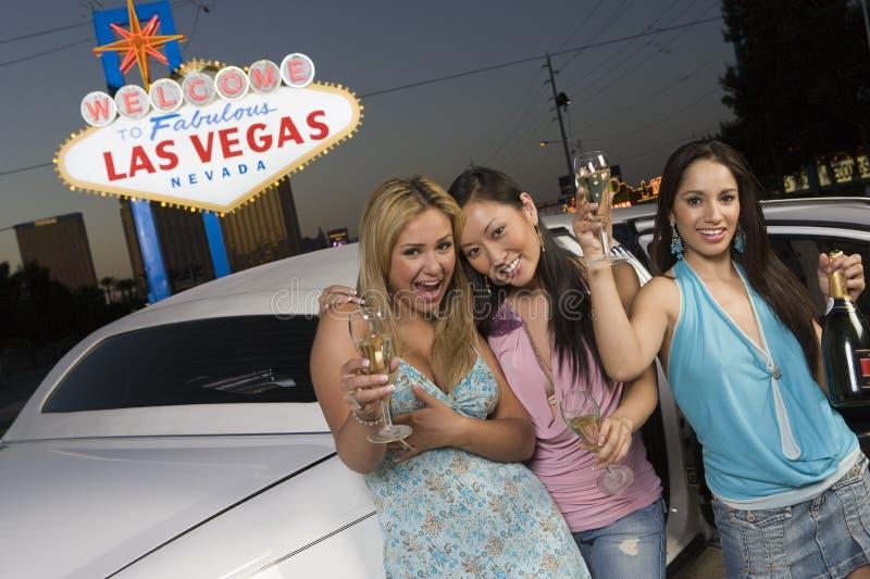 Kvinnliga vänner med Champagne Standing By Limousine royaltyfria foton