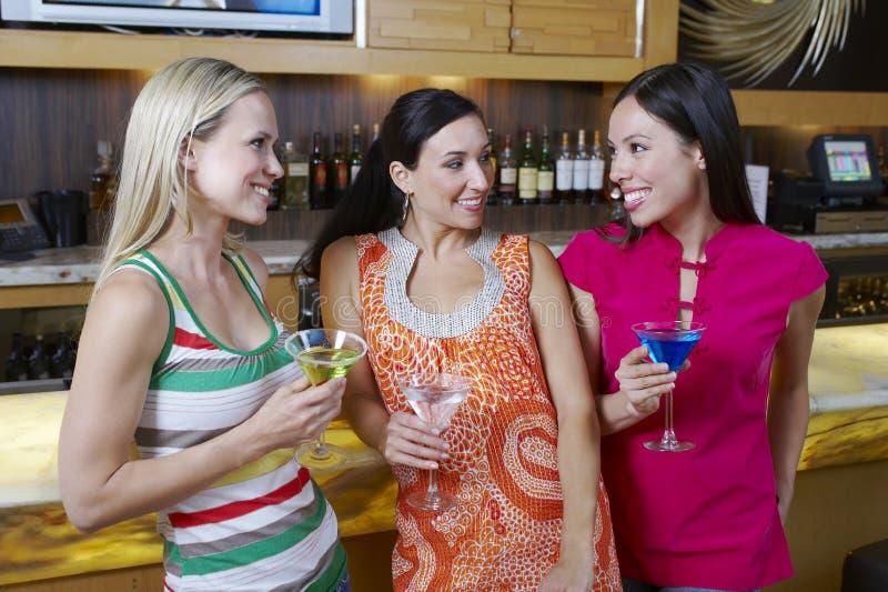 Kvinnliga vänner med drinkar på stången arkivfoto