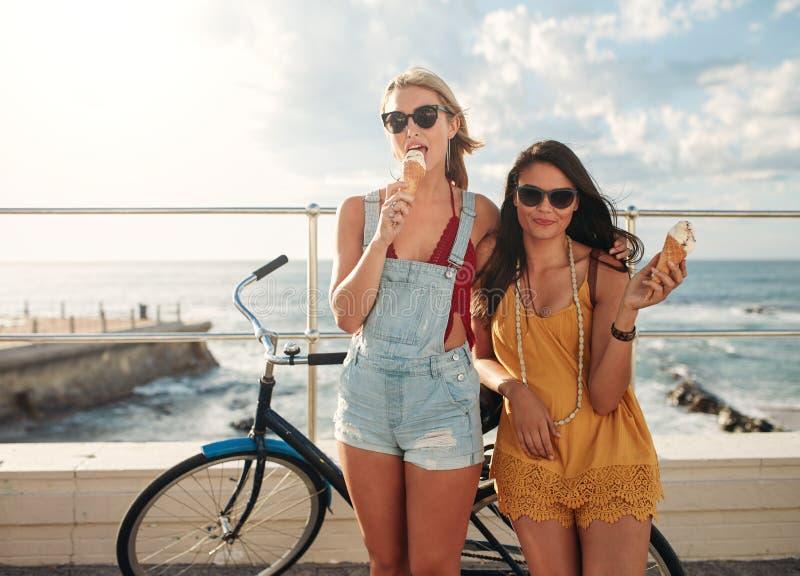Kvinnliga vänner med en cykel som äter glass fotografering för bildbyråer