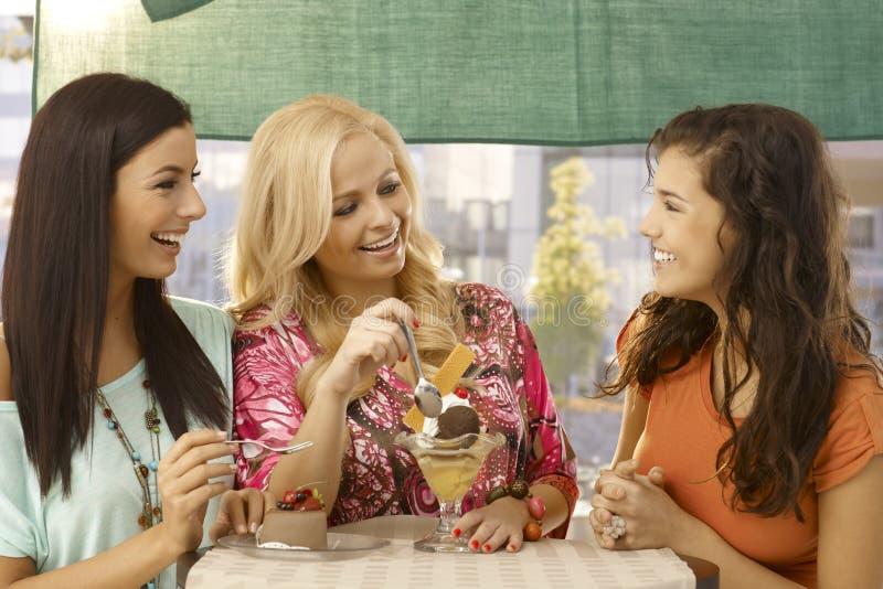 Kvinnliga vänner på att le för kafé arkivbilder