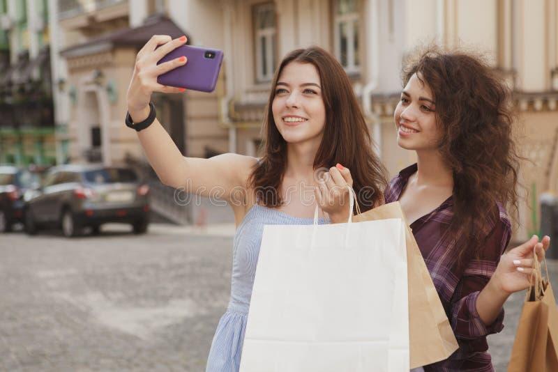 Kvinnliga vänner som använder den smarta telefonen, medan gå stadsgator royaltyfria bilder