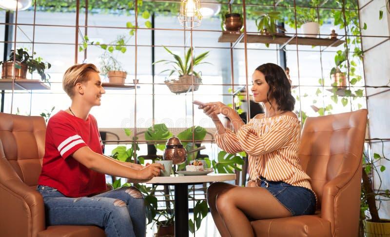 Kvinnliga vänner som dricker te med kakan på kafét fotografering för bildbyråer