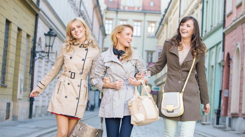 Kvinnliga vänner som går och skrattar arkivfoto
