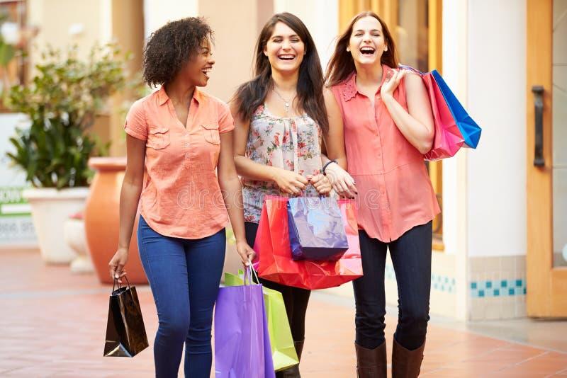 Kvinnliga vänner som går till och med galleria med shoppingpåsar royaltyfria bilder