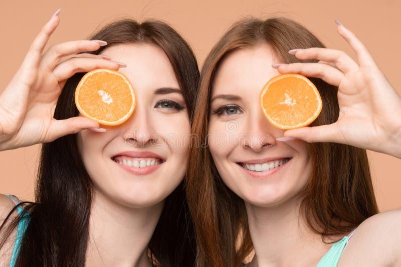 Kvinnliga vänner som håller nya apelsiner och poserar i studio arkivbild