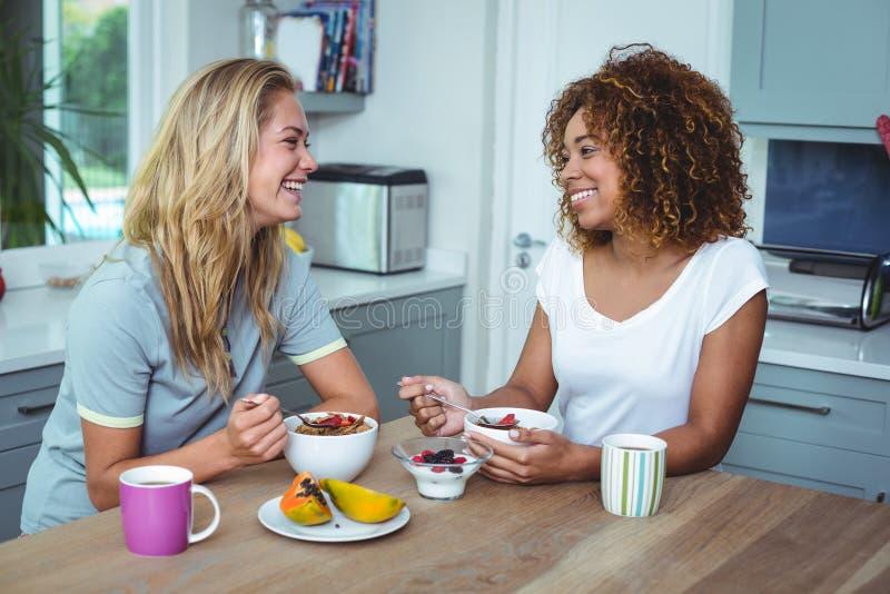 Kvinnliga vänner som har frukosten på köksbordet royaltyfri bild