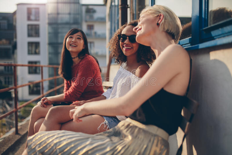 Kvinnliga vänner som har gyckel i balkong arkivbild