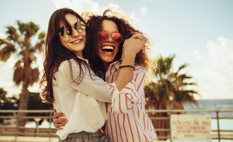 Kvinnliga vänner som har gyckel på dag ut royaltyfria foton