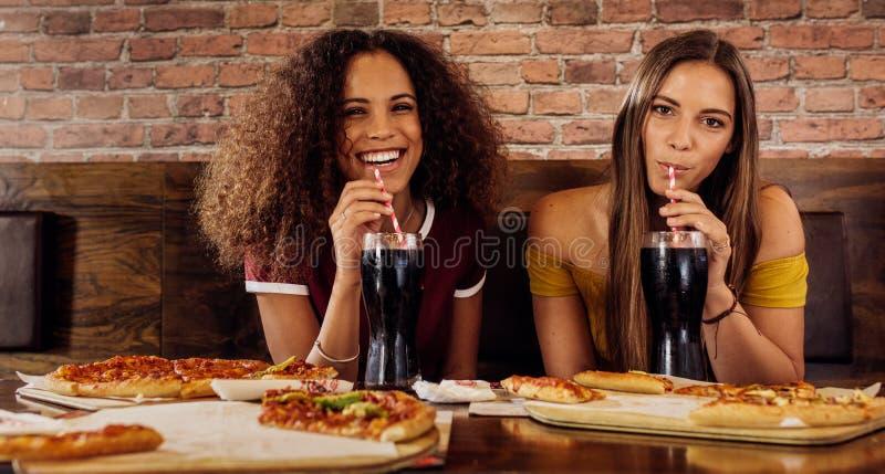 Kvinnliga vänner som har lunch på restaurangen royaltyfri bild