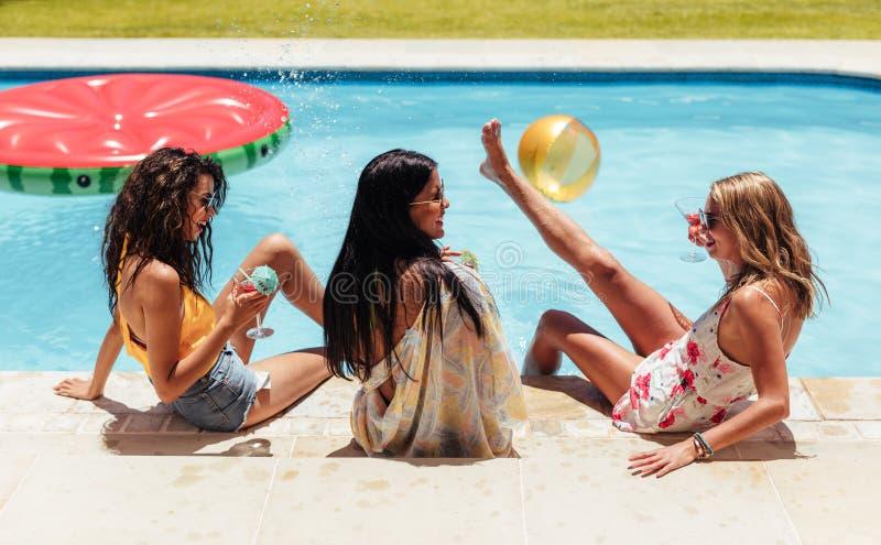 Kvinnliga vänner som har partiet av simbassängen royaltyfria foton