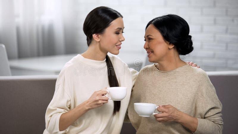 Kvinnliga vänner som har te, privat konversation mellan modern och dottern fotografering för bildbyråer