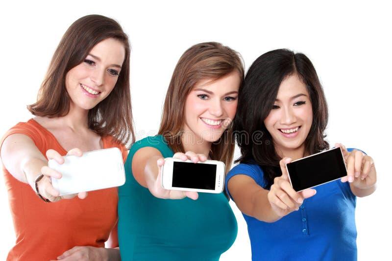 Kvinnliga vänner som tar en bild av dem arkivfoto