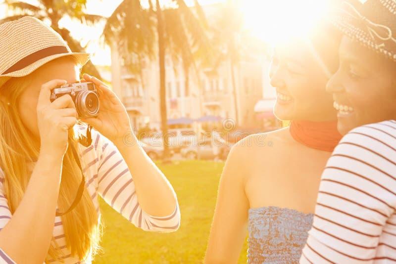 Kvinnliga vänner som tar fotografier av de parkerar in fotografering för bildbyråer