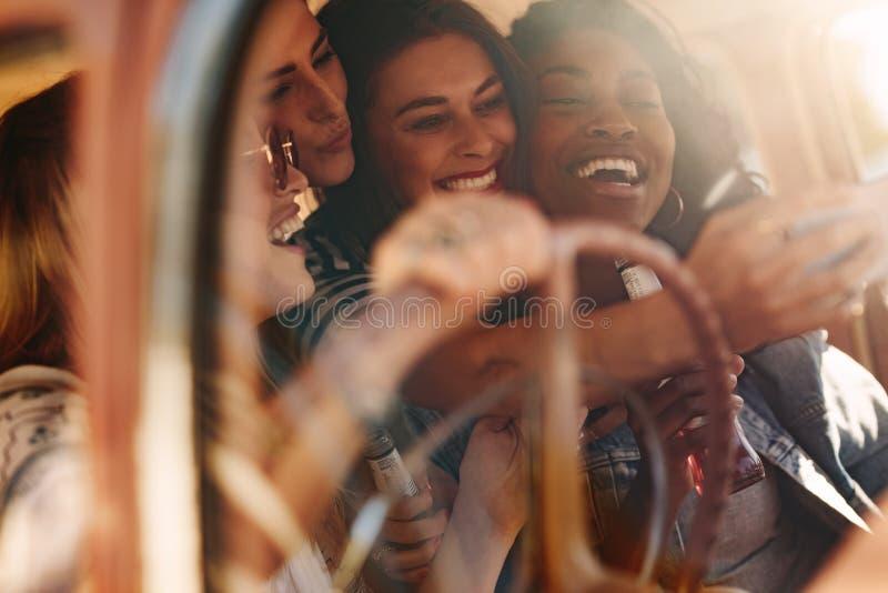 Kvinnliga vänner som tar selfie med i bilen arkivfoto