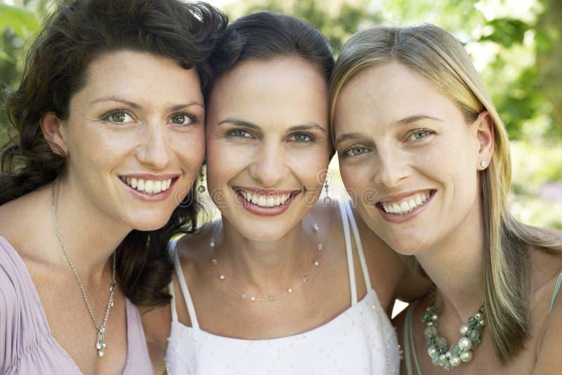 Kvinnliga vänner som tillsammans ler royaltyfri fotografi
