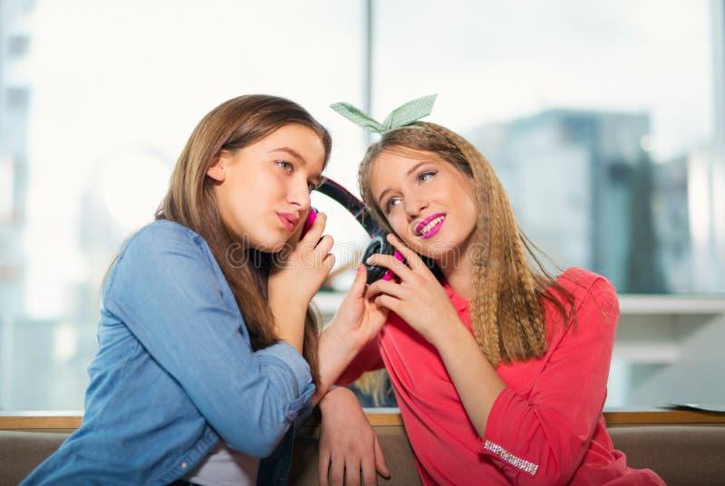 Kvinnliga vänner som tillsammans lyssnar till musik royaltyfri bild