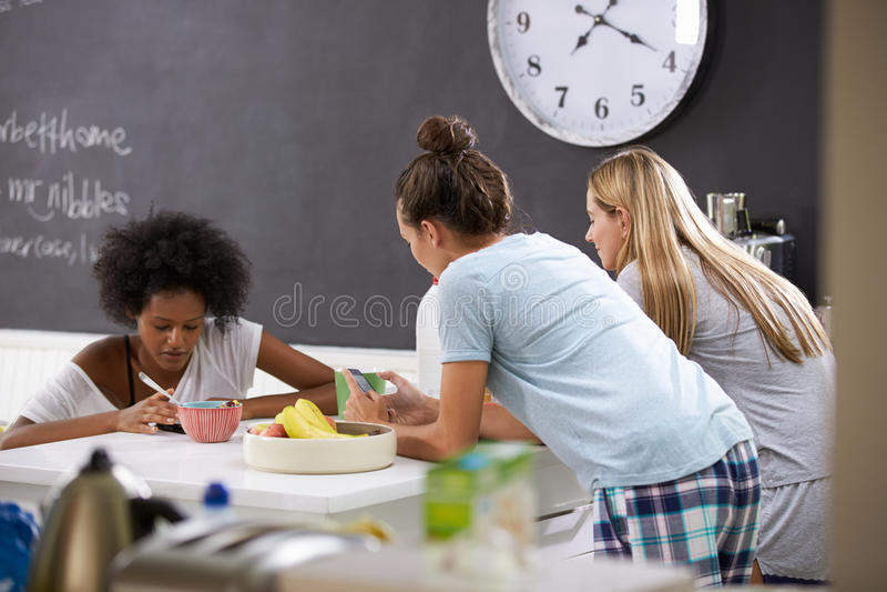 Kvinnliga vänner som tycker om frukoststunden som kontrollerar mobiltelefoner royaltyfri bild