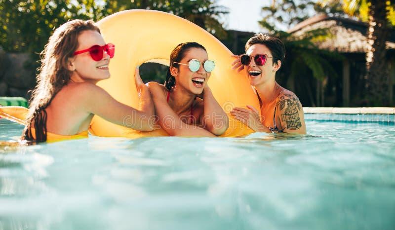 Kvinnliga vänner som tycker om sommar på pölen royaltyfria bilder
