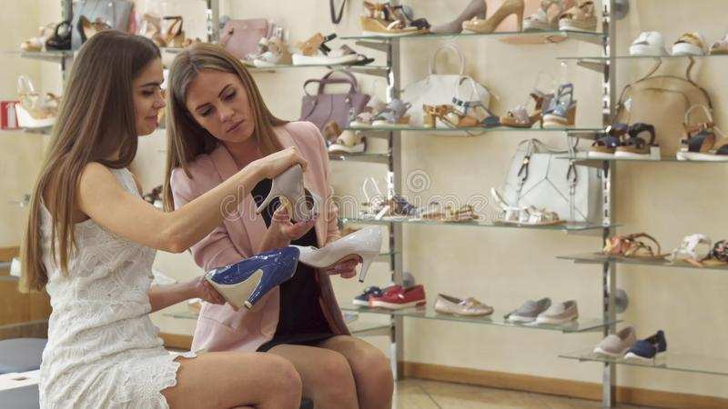 Kvinnliga vänner väljer mellan tre skor på shoppa arkivbilder