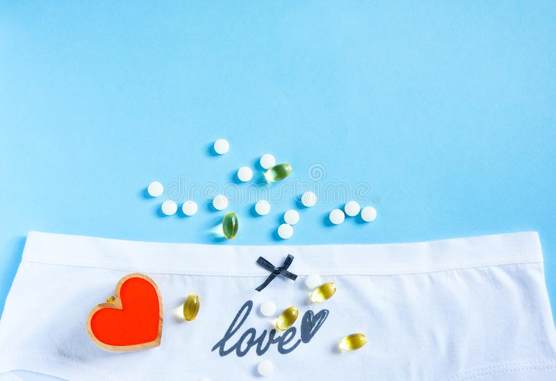 Kvinnliga vita trosor med växande bog och ordkärlek, hjärta och tabletter på blått gynekologi Hälso- och sjukvård, preventivmedel arkivfoton