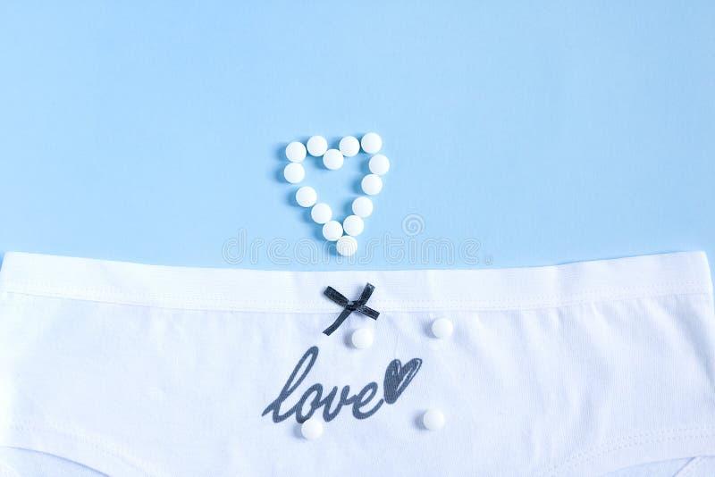 Kvinnliga vita trosor med växande bog och ordkärlek och segel på blått Gynekologi och erologi Hälso- och sjukvård, preventivmedel royaltyfri bild