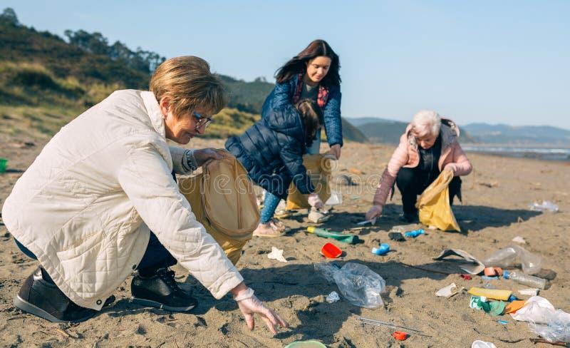 Kvinnliga volont?rer som g?r ren stranden arkivfoto