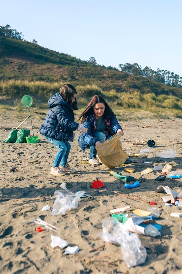 Kvinnliga volont?rer som g?r ren stranden royaltyfri bild
