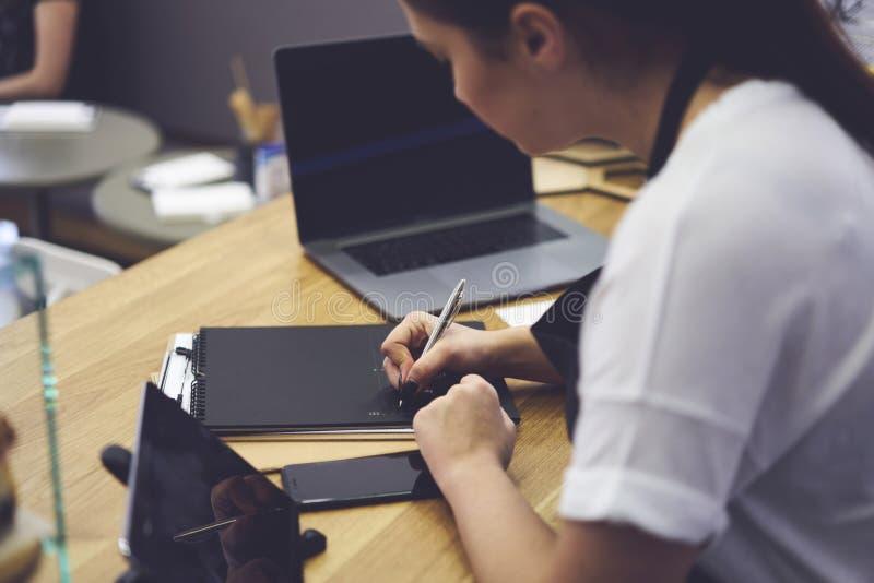 Kvinnliga waitres som skriver rapporten som använder information från bärbara datorn med åtlöje avskärmar upp royaltyfri fotografi