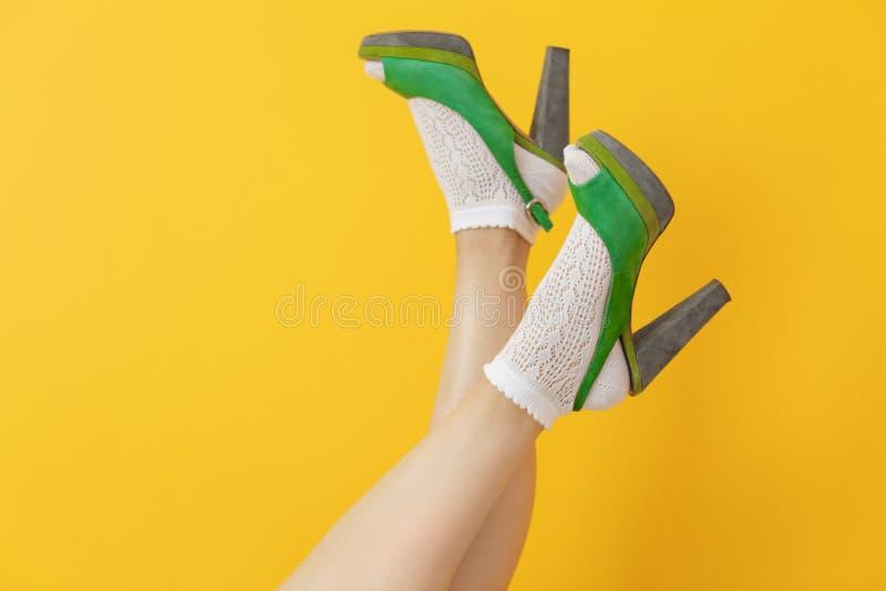 Kvinnligben i grön hög häl skor och sockor royaltyfri fotografi