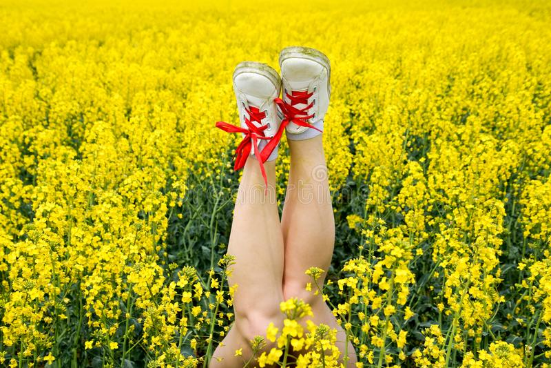 Kvinnligben i gymnastikskor som klibbar ut ur blommor ben upp Ben mot bakgrunden av guling våldtar blomningar fotografering för bildbyråer