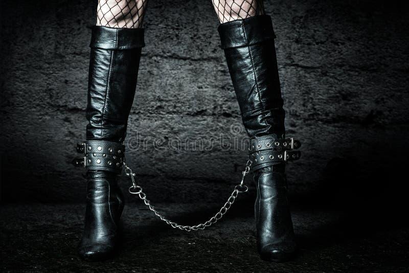 Kvinnligben i svarta kedjade fast läderkängor royaltyfria foton
